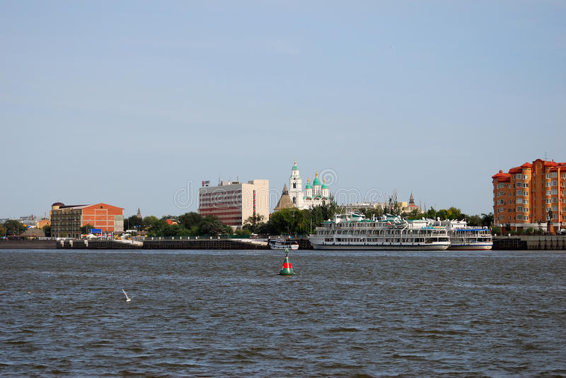 Kremlin in Askrahkan and other landmarks seen from the Volga river. Cruise liners are seen on the river. Modern architecture of the town (red and orange stock images
