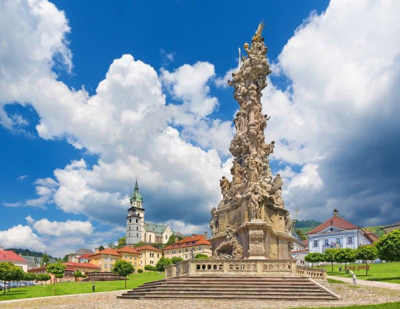 Kremnica - el cuadrado de Safarikovo la columna barroca de la trinidad santa de Dionyz Ignac Stanetti, castillo y St Catherine foto de archivo libre de regalías