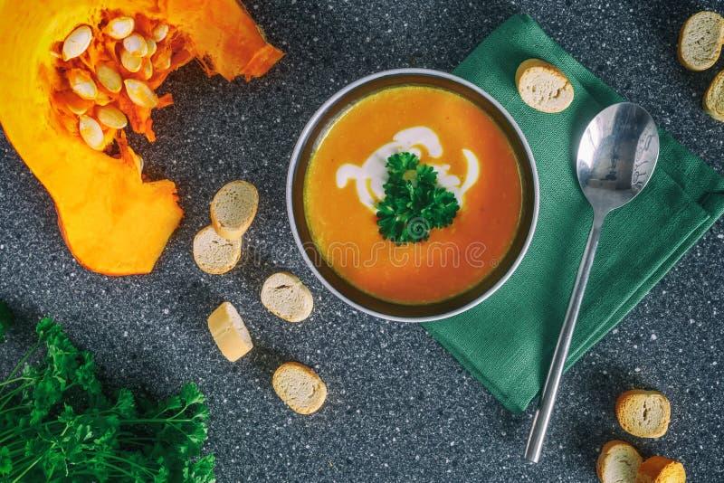 Kremowa dyniowa polewka z świeżymi ziele i krakers na zmroku drylujemy tło zdrowa żywność Selekcyjna ostrość Odgórny widok fotografia stock
