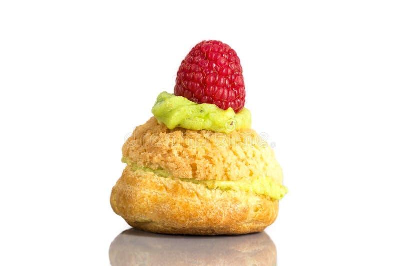 Kremowego chuchu torty lub profiterole z batożącą pistacjową śmietanką wypełniający słuzyć z stawberry dekoracją obrazy royalty free