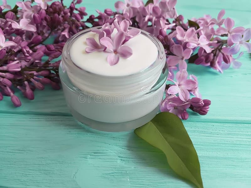kremowego moisturizer kosmetyczny lily kwiat domowej roboty relaksuje aromatycznego na błękitnym drewnianym backgrounextract d fotografia stock