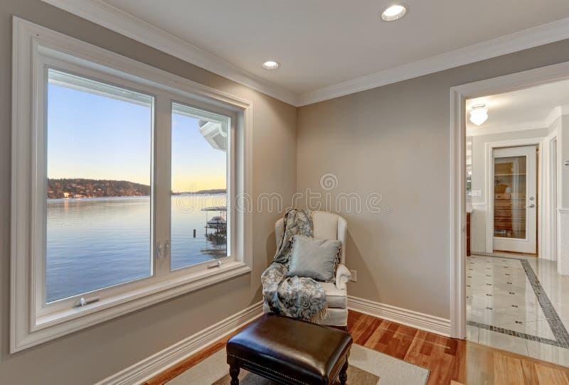 Kremowy siedzący pokój z wygodnym wingback krzesłem fotografia stock