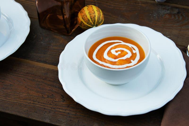 Kremowy zupny puree na tle dekoracyjna bania w ogródzie na drewnianym stole, właściwy odżywianie, zdrowi lifes fotografia royalty free