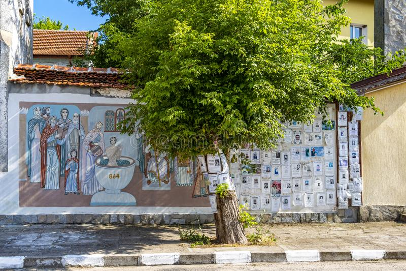 Death notices and a mural painting by the artists Christo Panev and Pancho Panev in the village of Krepost, Haskovo Province, royalty free stock images