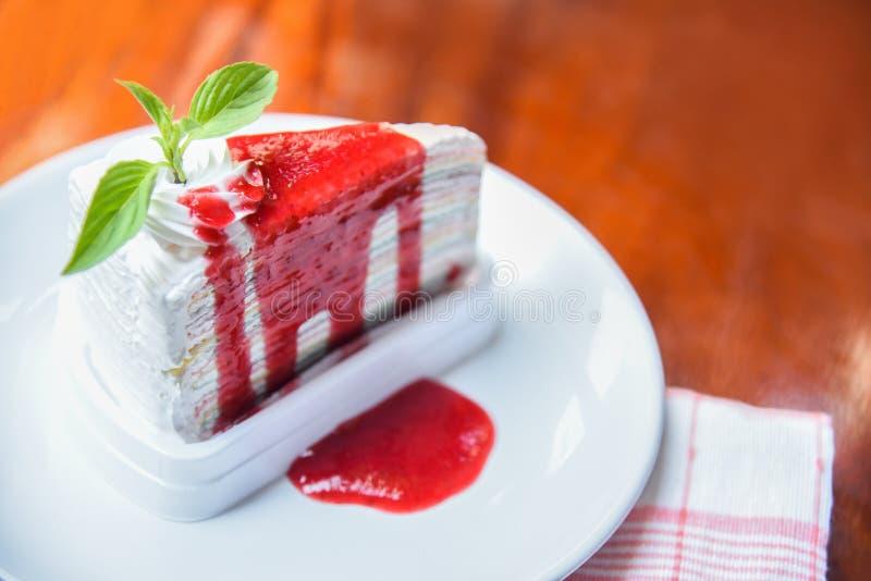 Kreppkuchenscheibe mit Erdbeersoße auf weißer Platte auf Tabelle/Stück Kuchenregenbogen stockbilder