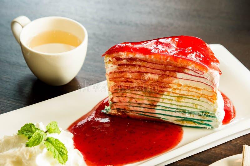 Kreppkuchenschicht-Regenbogenfarbe und Soßenerdbeernachtisch auf Tellerweiß im Café lizenzfreie stockfotografie