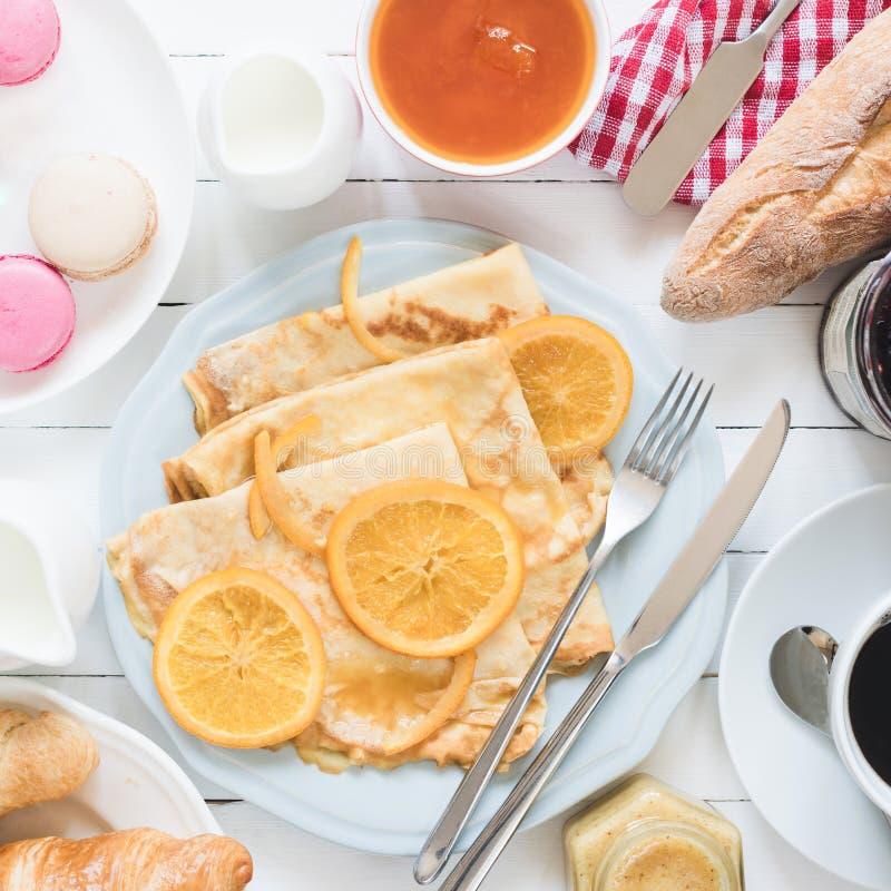 Krepy Suzette na talerzu, dżemu, baguette, kawie i macarons błękita, Tradycyjny francuski śniadanie fotografia royalty free