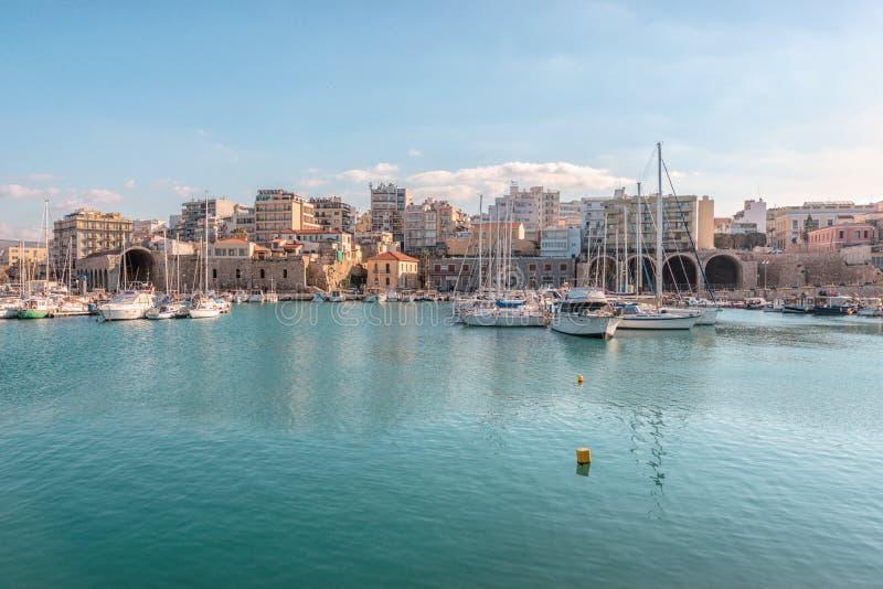Kreta Grekland - Februari, 11, 2019: Fartyg och yachter i porten p? bakgrunden av den Heraklion staden Grekland royaltyfri bild