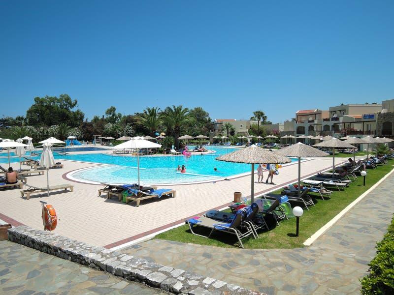 Kreta Grekland - Juni 15th, 2017: Härliga sikter av hotellet med simbassängen, soldagdrivare och familjer arkivfoton