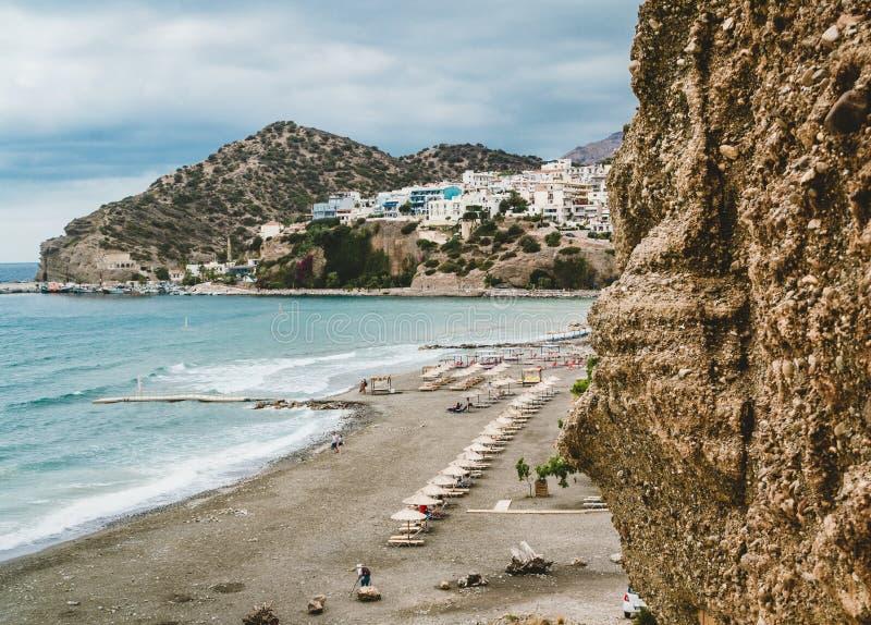 Kreta, Griekenland Mening van klippen aan dorp met mariene schepen, boten en vuurtoren Mening van klip op Baai met strand stock afbeelding
