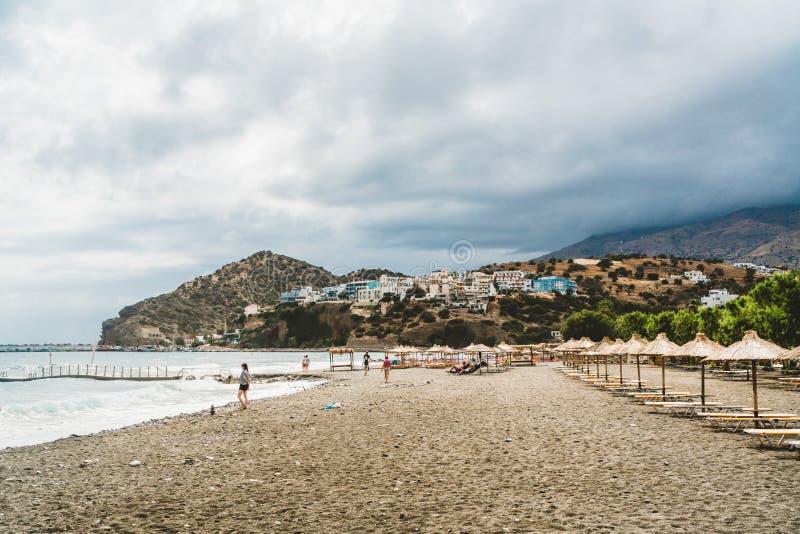 Kreta, Griekenland Mening van klippen aan dorp met mariene schepen, boten en vuurtoren Mening van klip op Baai met strand stock fotografie