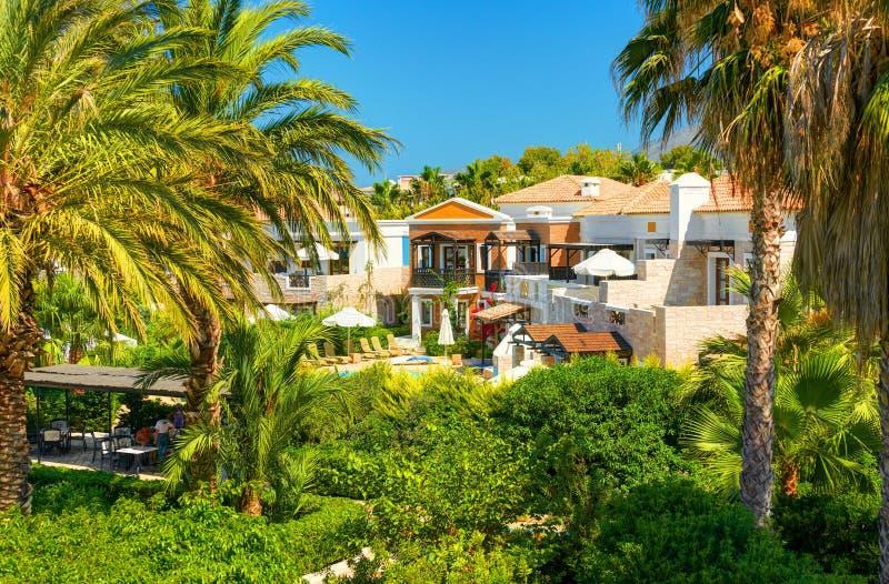 KRETA-INSEL, GRIECHENLAND, AM 1. JULI 2011: Ansicht über Hotellandhäuser für Touristengäste Grüner tropischer Palme-Swimmingpool, stockfotos