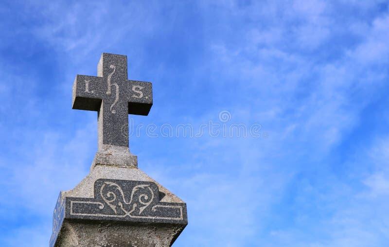 Kreuz auf alten Grabstein mit blauem Himmel im Hintergrund stockfotos