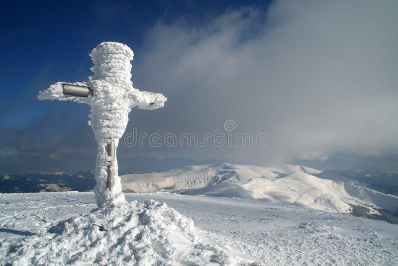 Kreuz auf dem Wintergipfel stockbild