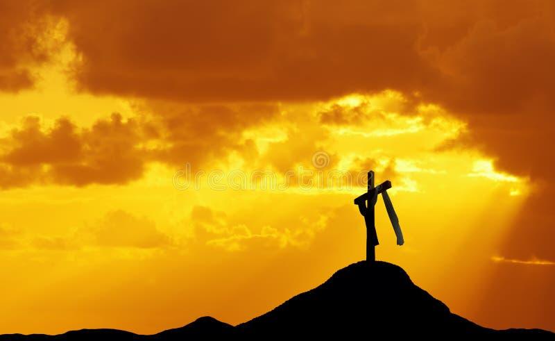 Kreuz auf Hügel bei Sonnenuntergang oder Sonnenaufgang stockbild