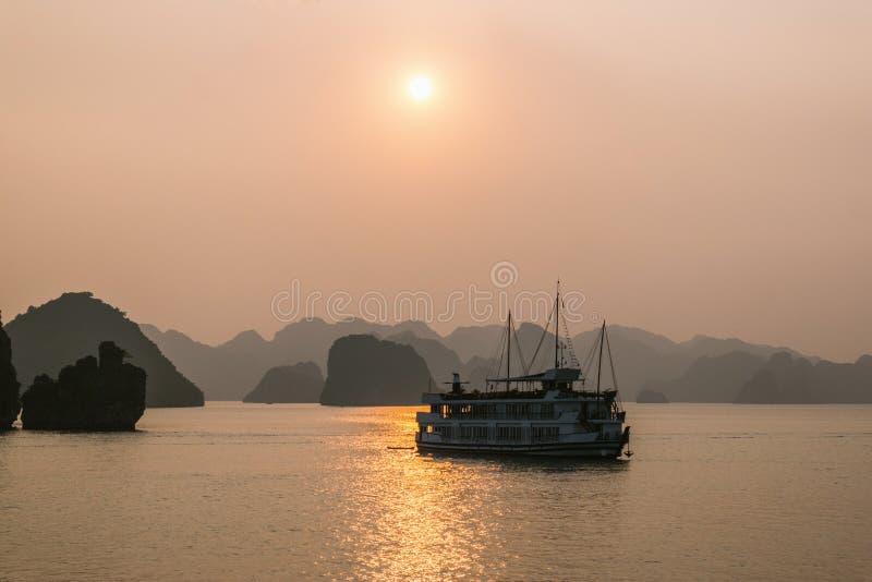 Kreuzfahrtboot an Sonnenuntergang Halong-Bucht stockbilder