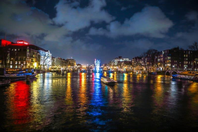 Kreuzfahrtbootseile in den Nachtkanälen Helle Installationen auf Nachtkanälen von Amsterdam innerhalb des hellen Festivals lizenzfreie stockfotografie