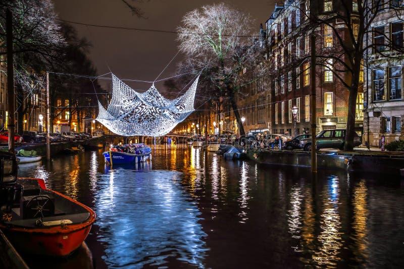 Kreuzfahrtbootseile in den Nachtkanälen Helle Installationen auf Nachtkanälen von Amsterdam innerhalb des hellen Festivals lizenzfreies stockfoto