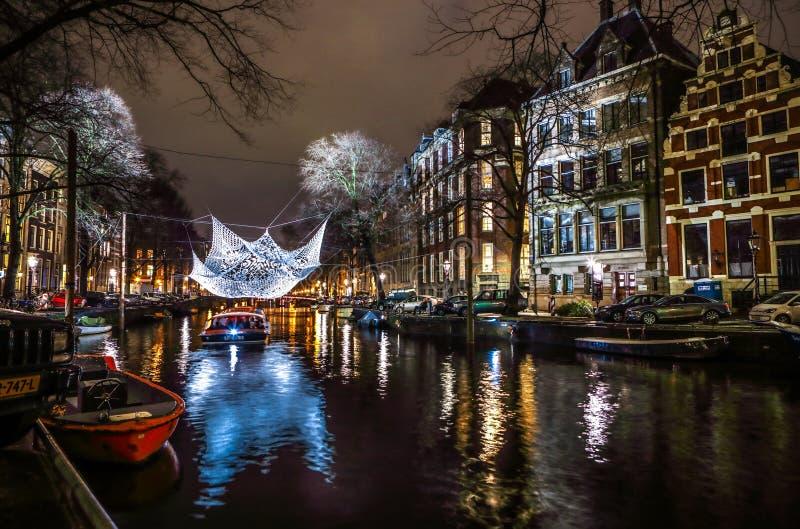 Kreuzfahrtbootseile in den Nachtkanälen Helle Installationen auf Nachtkanälen von Amsterdam innerhalb des hellen Festivals stockfotos