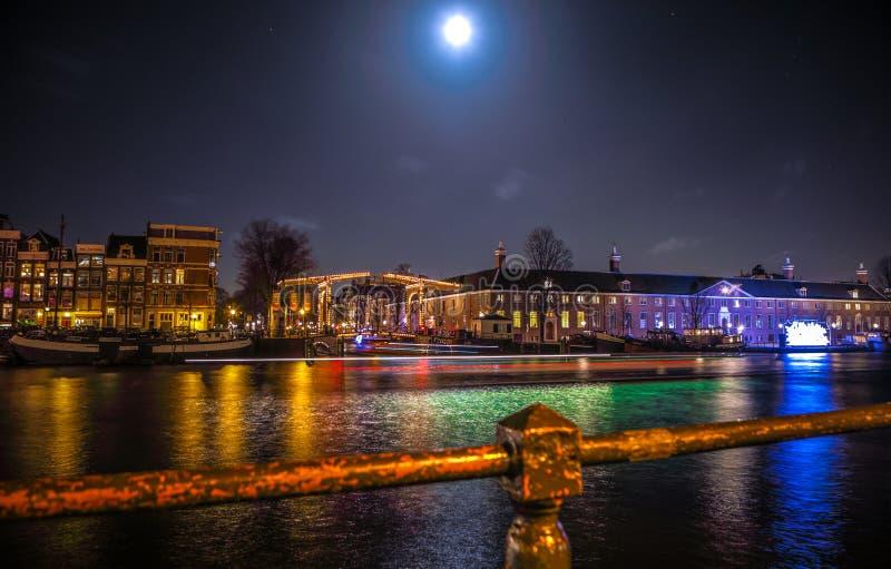 Kreuzfahrtbootseile in den Nachtkanälen Helle Installationen auf Nachtkanälen von Amsterdam innerhalb des hellen Festivals stockfoto