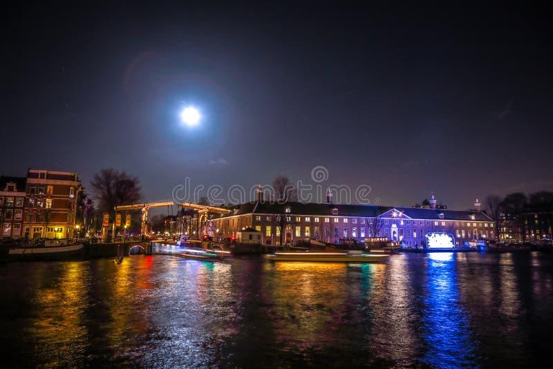 Kreuzfahrtbootseile in den Nachtkanälen Helle Installationen auf Nachtkanälen von Amsterdam innerhalb des hellen Festivals am Vol lizenzfreie stockfotos