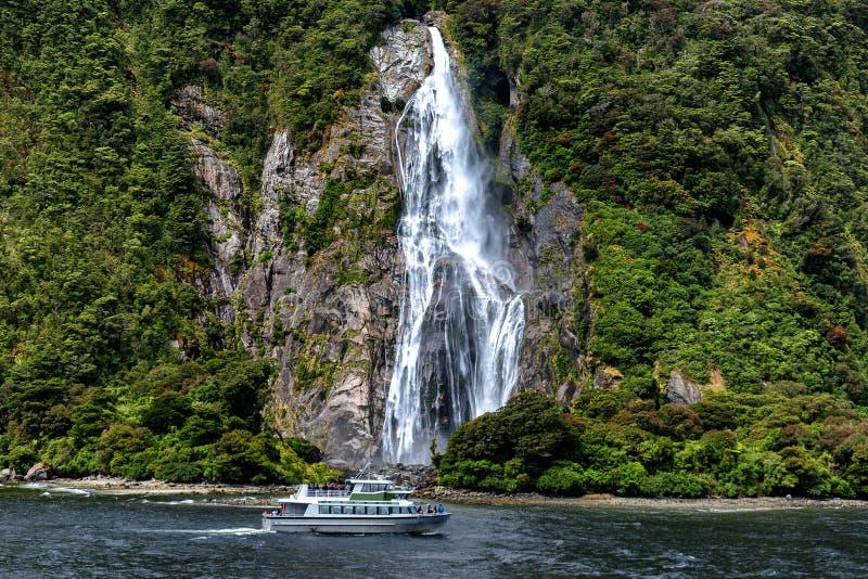 Kreuzfahrtfähre und schöner hoher Wasserfall in Milford Sound, Nationalpark Fiordland lizenzfreie stockfotografie