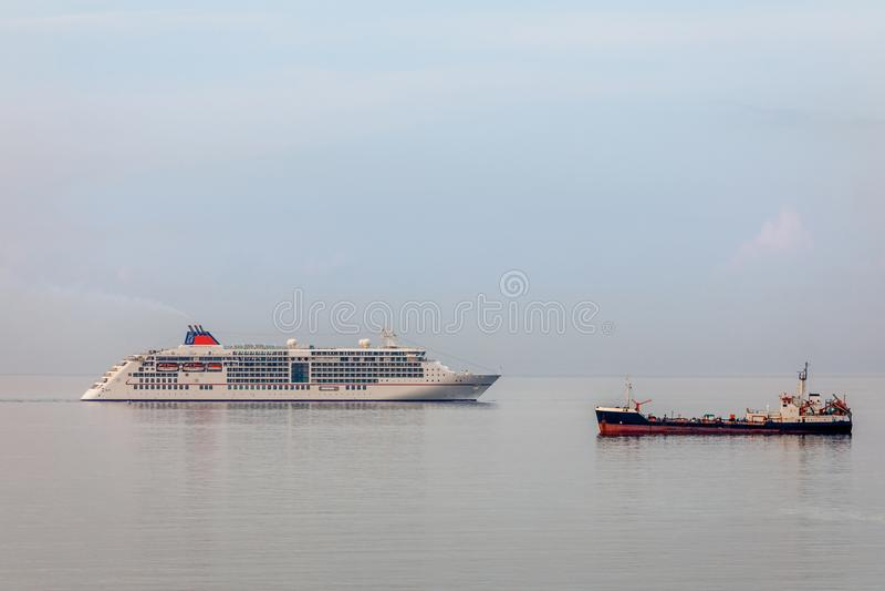 Kreuzfahrtschiff und Frachtschiff auf der Oberfläche im Limassol b stockfotos
