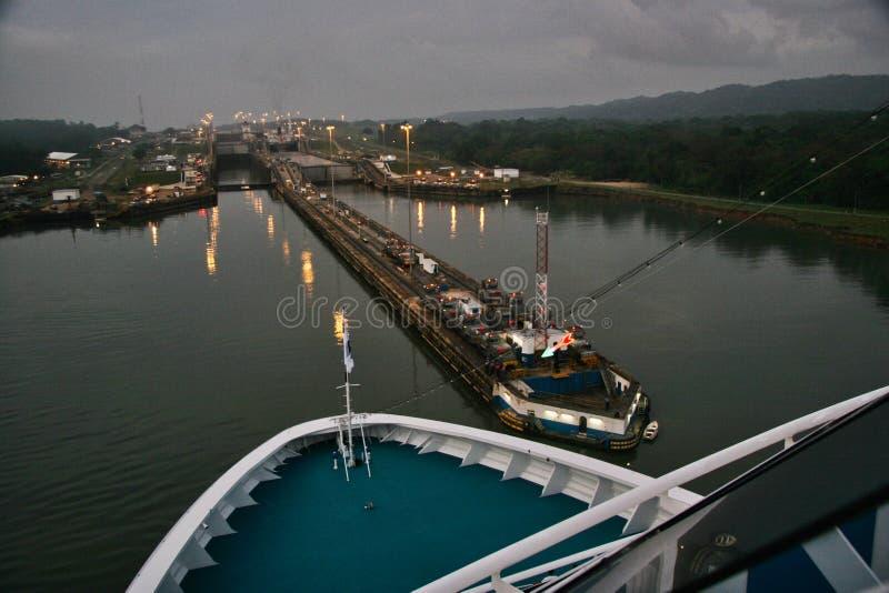 Kreuzschiff kommt Panamakanal an der Dämmerung stockbild
