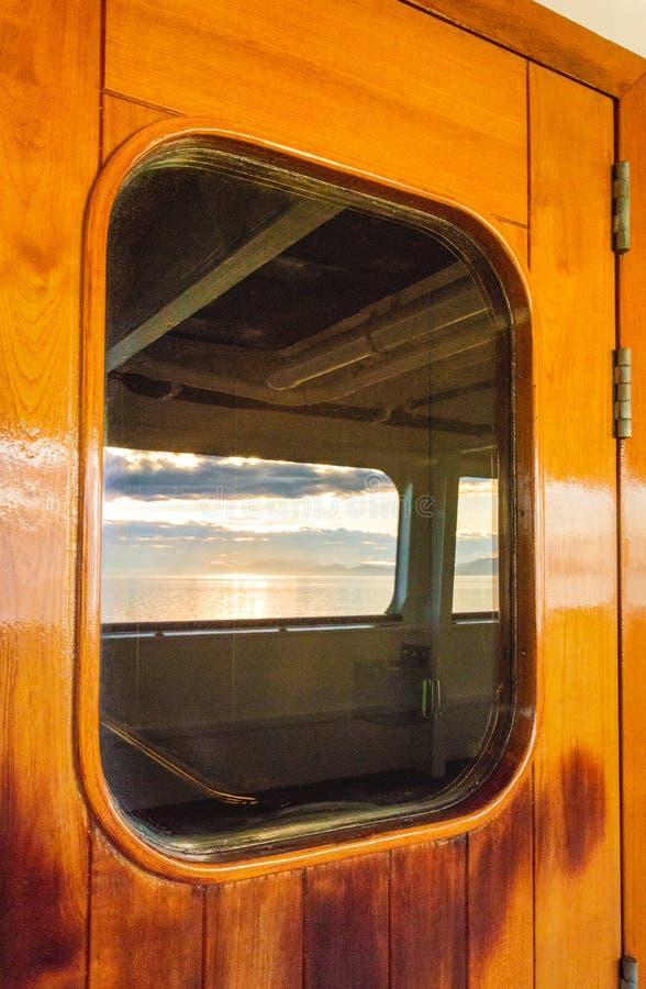 Kreuzschiffschwere hölzerne lackierte Außentür mit dem Fenster, welches das Meer reflektiert stockfotos