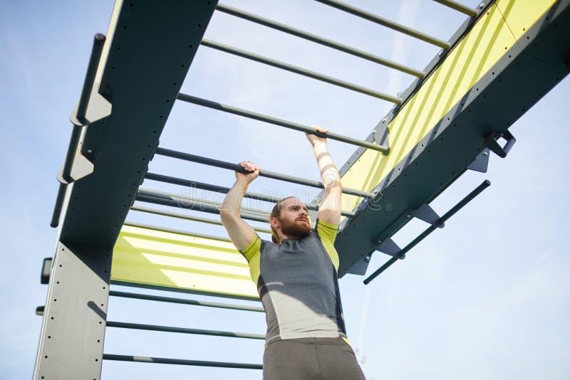 Kreuzungskletterstangen des Mannes stockbild