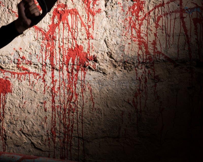 Krew plamiąca ściana i męska ręka trzyma saw zdjęcie stock