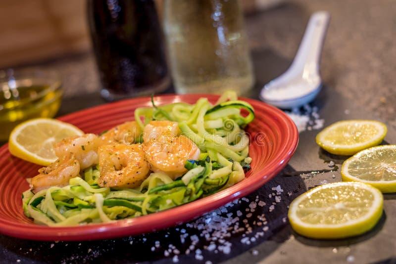Krewetkowy Scampi słuzyć nad zucchini kluskami smażonymi z cytryną, czosnkiem, masłem i ziele, fotografia stock