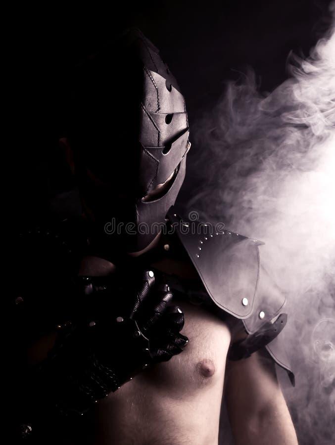 Krieger in der Maske im abstrakten Rauche auf schwarzem Hintergrund stockfoto