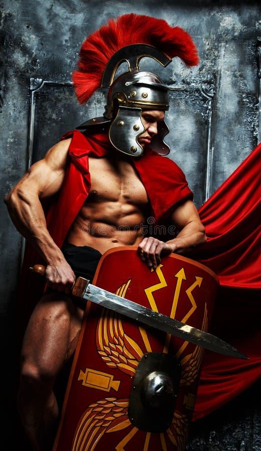 Krieger mit ausgebildetem Körper hält swor und Schild stockbild