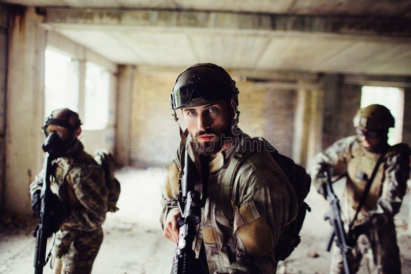 Krieger stehen im leeren Raum Sie gehen vorwärts sehr vorsichtig Kerle auf den speziellen Gesichtsmasken der hinteren Abnutzung s stockbilder