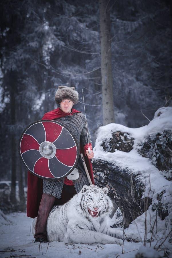 Krieger steht über einem weißen Tiger Knurrens lizenzfreie stockfotografie