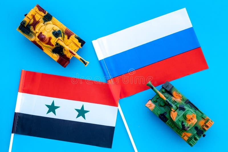 Krig konfrontationbegrepp Ryssland Syrien Behållareleksak nära ryss och syriansk flagga på bästa sikt för blå bakgrund arkivfoton