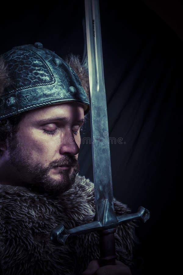 Krig-, Viking krigare med järnsvärdet och hjälm med horn arkivfoton