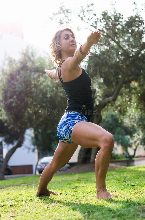 Krigare en för yoga för yogakonditiondemonstrationen poserar Virabhadrasana en, av den härliga unga caucasian kvinnan som bär kon arkivfoton