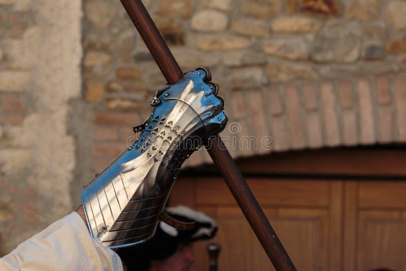 Krigare med den medeltida metalliska tumvantet för handskydd och träpinne arkivbild