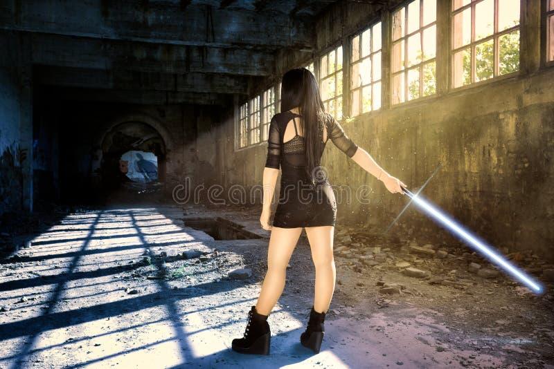 Krigarekvinna med en lightsaber som väntar på hennes motståndare arkivfoton