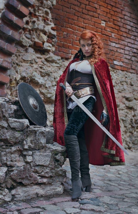 Krigarekvinnan med svärdet i medeltida kläder är mycket farlig royaltyfri foto