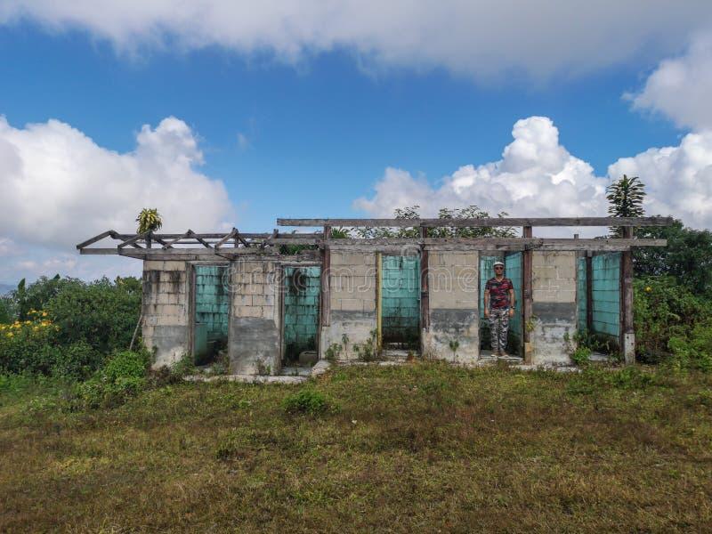 Krigareman som är målskyttet i övergiven byggnad med att förbluffa bakgrund för molnig himmel arkivfoto