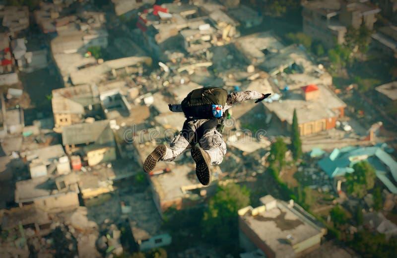 Krigsmakter med hoppa fallskärm i överkant av den förstörda staden royaltyfri fotografi