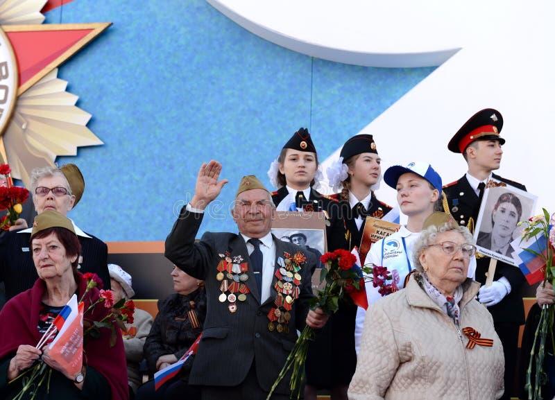 Krigsveteran välkomnar deltagarna av `en för regementet för handling` den odödliga på den röda fyrkanten av Moskva royaltyfria bilder
