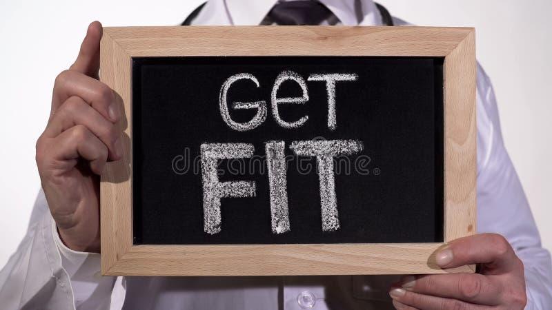Krijg geschikt op bord in artsenhanden geschreven, actieve gezonde het levensbevordering stock fotografie