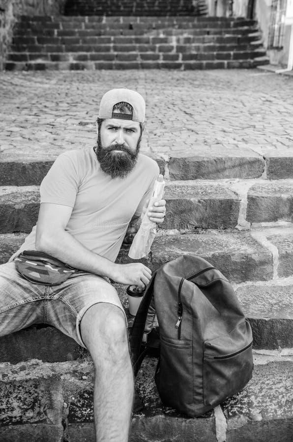 Krijgend wat rust en meer wandelend Het Kaukasische hipster ontspannen op treden met wandelingsrugzak Gebaarde mens die maaltijd  royalty-vrije stock fotografie