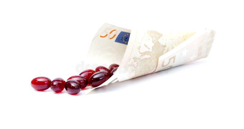Krill nafciane kapsuły, isolatKrill nafciane kapsuły, rozlewają out od euro banknoteed na bielu zdjęcia stock