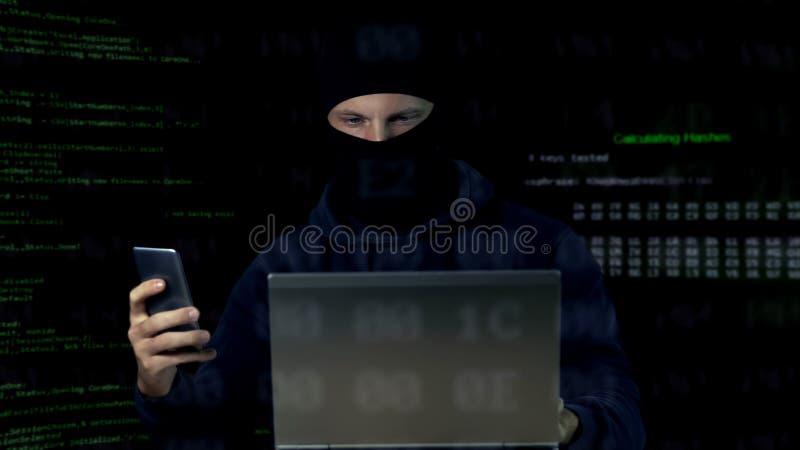 Kriminell bei Maskenprüfkamera auf Laptop und Telefon, Datenbank lizenzfreie stockfotografie
