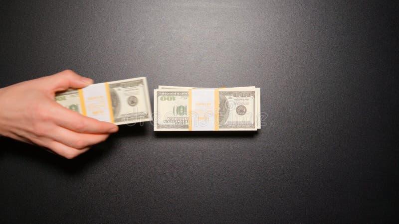 Kriminell - Geschäftsmanndiebstahl ein Geld von einem Stapel auf einer Tischplatteansicht stockfotos